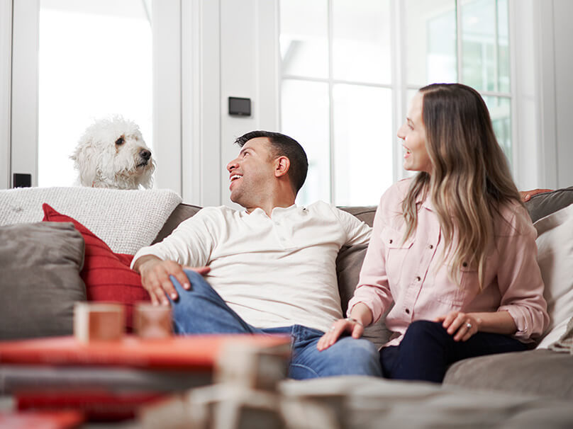 Couple sitting on the couch with a dog